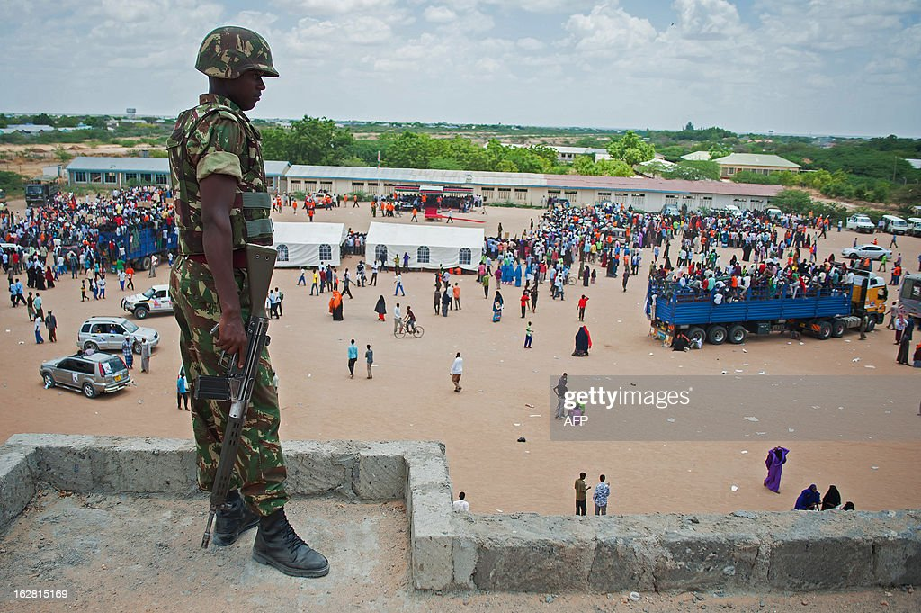 A Kenyan Defence Forces (KDF) soldier stands on a rooftop watching ODM (Orange Democratic Movement) supporters in Garissa Stadium during an ODM/CORD rally on February 27, 2013. Garissa, in Eastern Kenya, has seen regular violence in recent months, attributed by many to the instability in neighbouring Somalia. AFP PHOTO/Will Boase