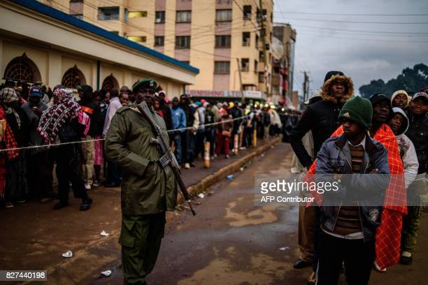 A Kenyan Defense Force member stands by as Kenyans wait in line to cast their ballot in the general elections at a polling station in the Rift Valley...