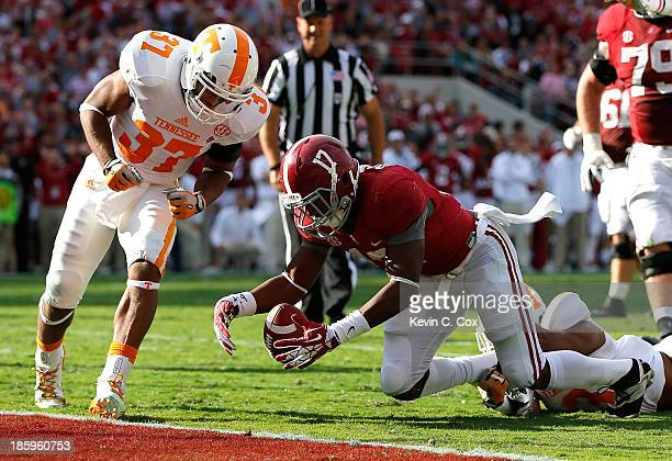 Kenyan Drake of the Alabama Crimson Tide fumbles the ball as he is tackled by Byron Moore of the Tennessee Volunteers at BryantDenny Stadium on...