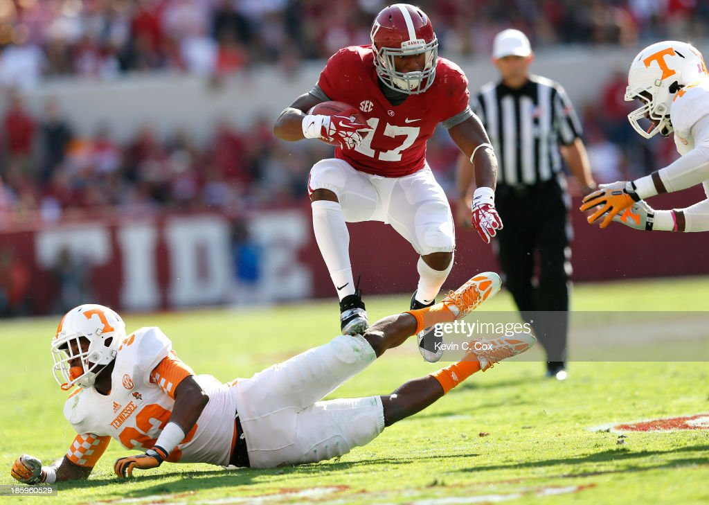 Kenyan Drake #17 of the Alabama Crimson Tide rushes over LaDarrell McNeil #33 of the Tennessee Volunteers at Bryant-Denny Stadium on October 26, 2013 in Tuscaloosa, Alabama.