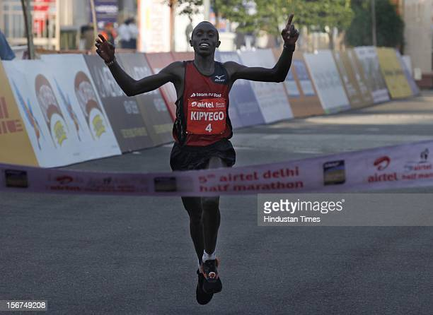'NEW DELHI INDIA SEPTEMBER 30 Kenyan Edwin Kipyego reacts after crossing the finishing line for victory in the 2012 Airtel Delhi halfmarathon on...