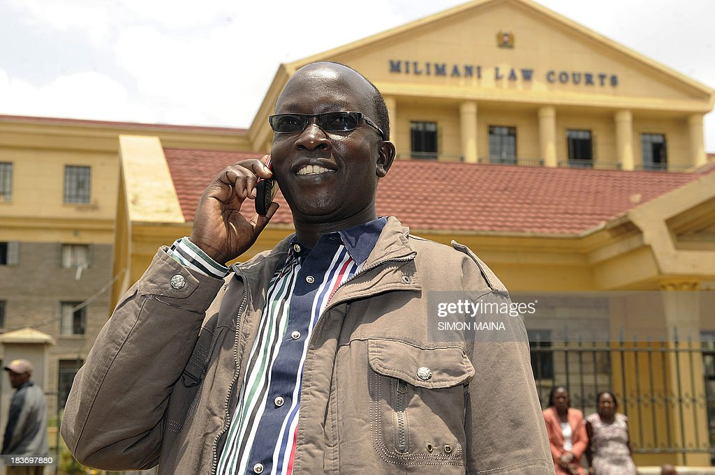 Kenyan ex-journalist Walter Barasa talks on October 9, 2013 on his cellular telephone outside the Nairobi Law court, where he appeared to file an urgent application to stop his arrest and handing over to the International Criminal Court (ICC). The International Criminal Court said on October 2 it had issued a warrant for the arrest of Walter Barasa for allegedly trying to bribe witnesses to drop their testimony in the crimes against humanity trial of Deputy President William Ruto. Barasa, 41, 'is charged with several offences against the administration of justice including corruptly influencing or attempting to corruptly influence ICC witnesses,' the Hague-based ICC said in a statement. MAINA