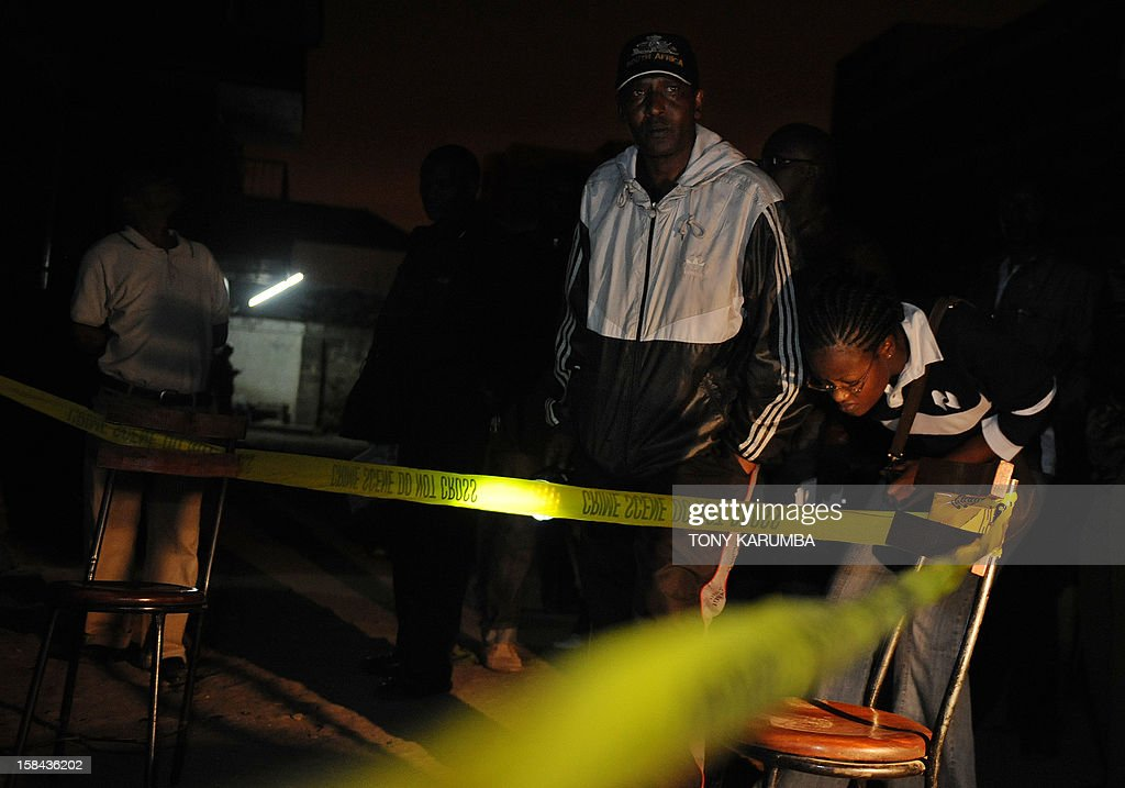 Kenyan forensic officers work around the sight of a grenade attack on December 16, 2012 in Nairobi's mainly Somali ethnic neighbourhood of Eastleigh. A huge blast shook the predominantly Somali neighbourhood of Eastleigh in the Kenyan capital Nairobi this evening after three grenades targeted at a local bar and restaurant were lobbed injuring at least two people, police said. Witnesses say there were at least three separate blasts and that the explosions occurred near a bar, which follows another recent grenade attack outside a mosque in the same neighbourhood that killed at least five people as well as wounding the local member of parliament. AFP PHOTO/Tony KARUMBA