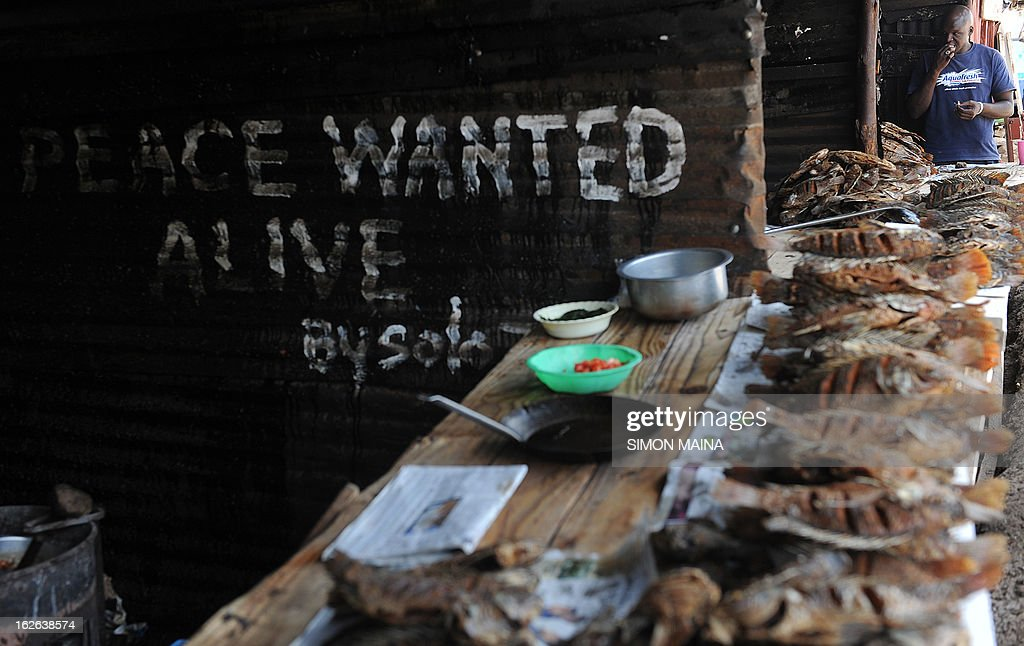 A Kenyan man eatS fish by the road side next to writing on an corrugated iron sheet house, urging for a peaceful poll on February,25,2013 in the sprawling Kibera slums. Kenya is gearing up for presidential, gubernatorial, senatorial elections on March 4, the first since bloody post-poll violence five years ago in which more than 1,100 people died after contested results. AFP PHOTO/SIMON MAINA