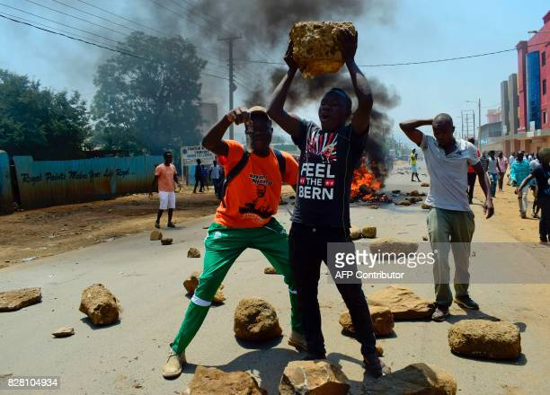TOPSHOT Kenyan National Super Alliance supporters hold rocks as they stand in front of a burning barricade on a road in Kisumu on August 9 as they...