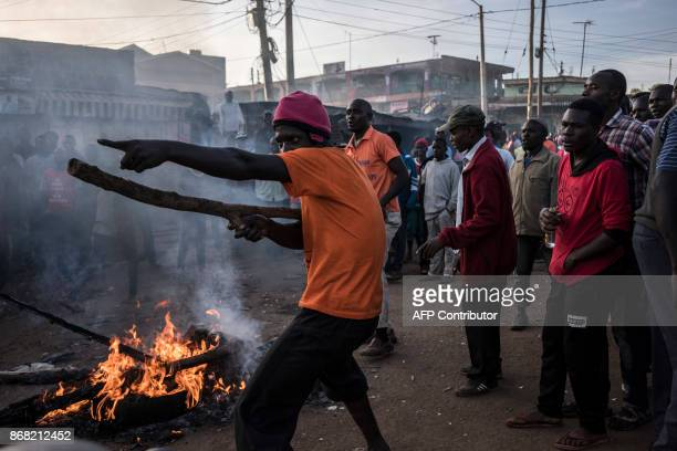TOPSHOT Kenyan opposition supporters gesture towards Kenyan riot police as they wait for the reelections results on October 30 2017 at Kawangware in...