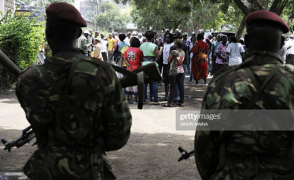 Kenyan paramilitaries stand guard at a polling station as people gather outside, in the Nairobi slum of Mathare on March 6, 2013, as Kenyans awaited presidential results with growing frustration at controversial delays and mountains of spoiled ballots, five years after violence sparked by a disputed tallying process.
