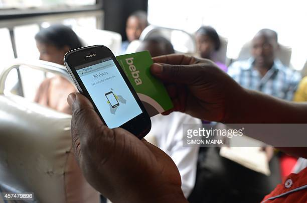 A Kenyan passenger uses on June 25 2014 a mobile phone and a 'BebaPay' card a mobile phonebased money transfer service that allows transit passengers...