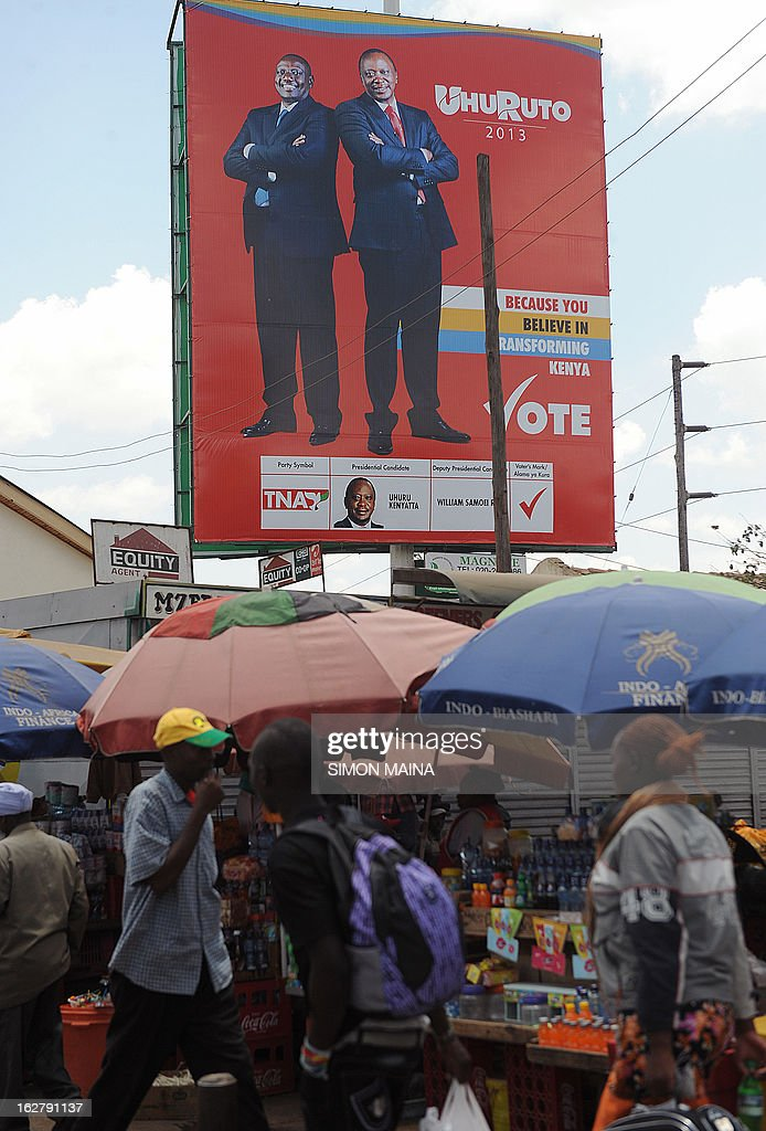 Kenyan people walk at an open air market next to a large campaign billboard advertising Presidential candidate Uhuru Kenyatta and his running-mate William Ruto, on the outskirts of Nairobi, Kenya on February 27, 2013. Kenya is gearing up for presidential, gubernatorial, senatorial elections on March 4, the first since bloody post-poll violence five years ago in which more than 1,100 people died after contested results. AFP PHOTO/SIMON MAINA