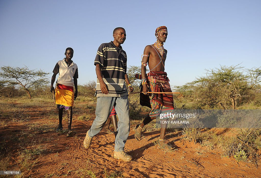 Kenyan poacher turned gamekeeper Kuyaso Lokoloi (C), 25, patrols on February 5, 2013 with his peers through part of a conservancy in Laikipia, approximately 250 kms north of the capital Nairobi, in search of poachers. Just Just a year ago he would have been on the lookout for game to poach in the thick acacia scrub that makes up the remote Samburu district, a key reserve for the increasingly threatened African elephant. Now, after risking death with armed wildlife rangers hunting him, the poacher has turned gamekeeper to go out patrolling to protect the animals he once killed. AFP PHOTO / TONY KARUMBA