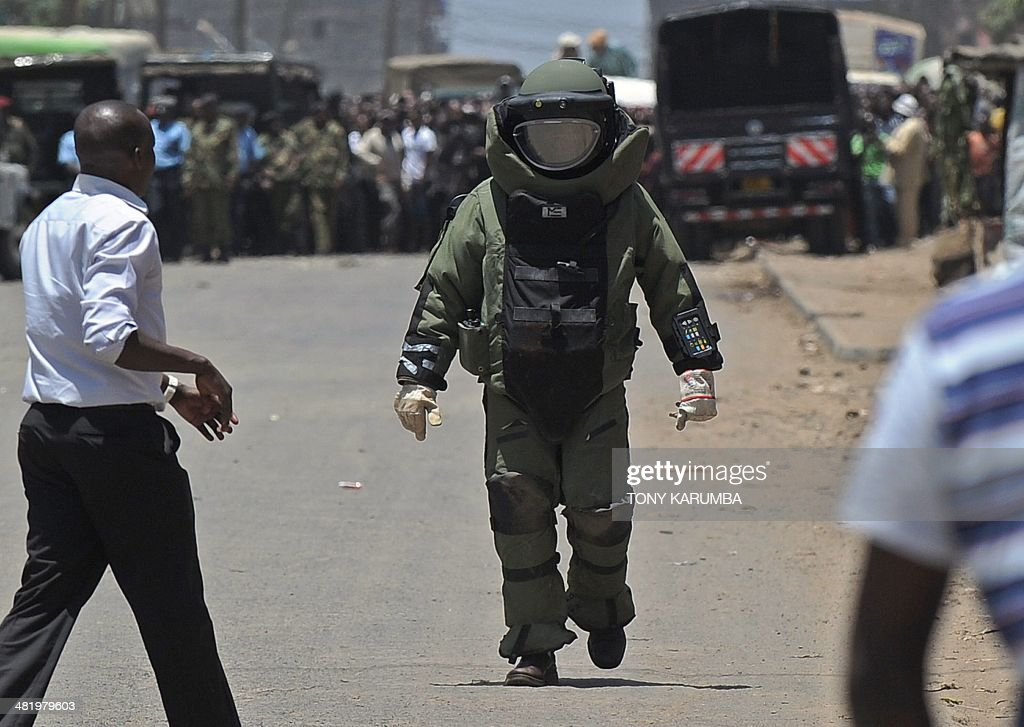 A Kenyan police bomb expert clad in a protective ballistic suit approaches the site of a suspected improvised explosive device, IED, on April 2, 2014 in Nairobi's increasingly restive Somali district of Eastleigh, a day after a prominent hardline Muslim cleric was shot dead in Mombasa. The cleric Abubaker Shariff Ahmed, was a vocal supporter of Osama bin Laden, and was on UN sanctions lists accused of being a 'leading facilitator and recruiter of young Kenyan Muslims for violent militant activity in Somalia', and of having 'strong ties' with Shebab leaders. AFP PHOTO/Tony KARUMBA