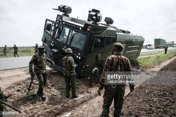 Kenyan police look on as a water cannon becomes stuck in the shoulder of a road following a demonstration with supporters of Kenyan's opposition...