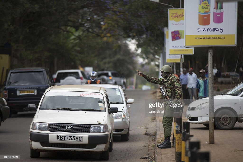 A Kenyan police officer deployed near the Westgate mall stands guard on September 28, 2013 in Nairobi, Kenya. Officals begun the task of forensic probing the Westgate shopping mall following a four-day siege that killed at least 67 civilians and police and was claimed by the Somali militant group al Shabaab.