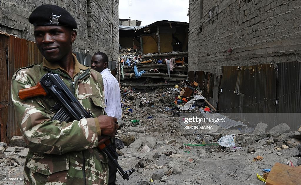 A Kenyan police officer stands on May 3, 2016 next to the the rubble of the six-storey building that collapsed killing 23 people in Nairobi's suburb of Huruma. Kenyan rescuers pulled an 18-month-old toddler alive from the rubble of a six-storey building on May 3, four days after the block collapsed killing 23 people, police said. Located in the poor, tightly-packed Huruma neighbourhood, the building had been slated for demolition after being declared structurally unsound. But an evacuation order for the structure, which was built near a river just two years ago, was ignored. MAINA