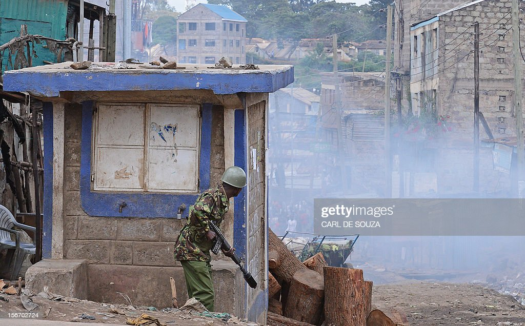 A Kenyan police officer takes cover in the somali district of Eastleigh in Nairobi on November 19, 2012. Police used tear gas and fired into the air to contain the violence which erupted after a bomb exploded in Eastleigh on November 18 2012 killing seven people and wounding many more. Kenyan residents in Eastleigh turned on Somalis and attacked their shops and stalls, accusing them of being responsible for the bomb.