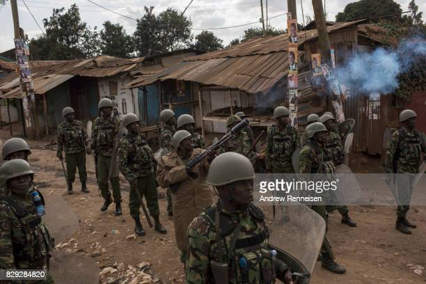 Kenyan police officers shoot tear gas to clear a street of protestors in the Kawangware slum on August 10 2017 in Nairobi Kenya Tensions remain high...