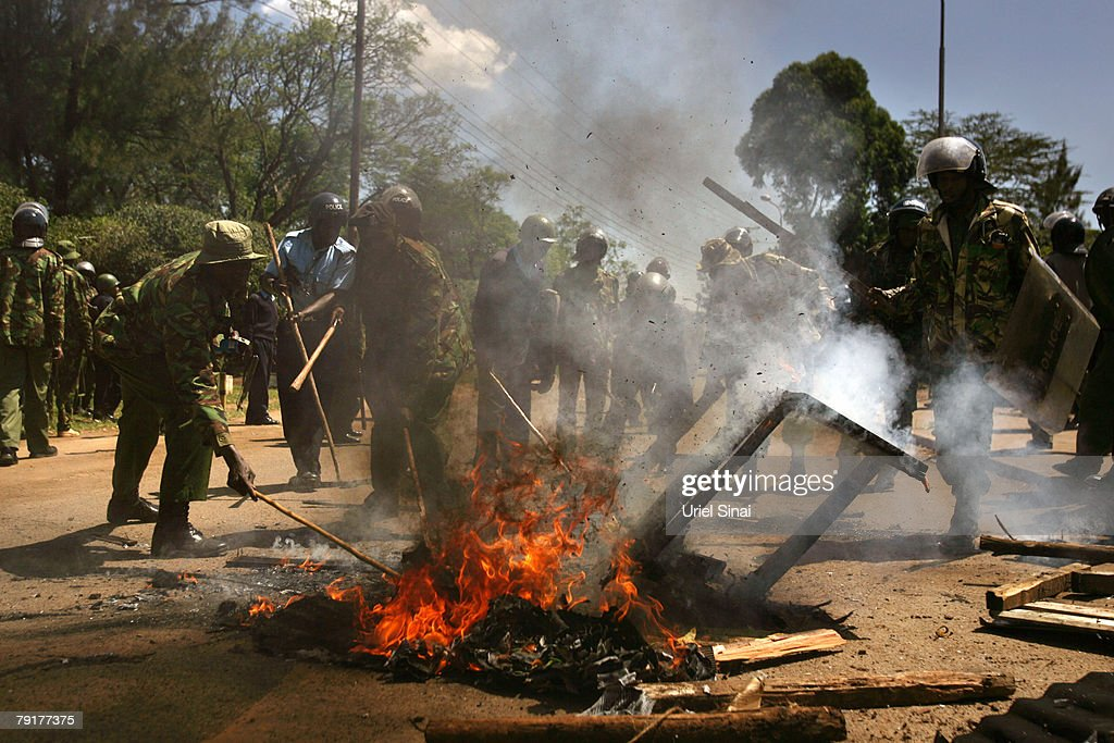 Kenyan police put out a fire after riots began during a mass funeral for the victims of clashes on January 23, 2008 in Nairobi, Kenya. More than 600 people have died in post-election violence after allegations election manipulation by the incumbent president sparked riots in the African nation.