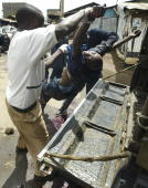 Kenyan policemen pick up the body of a man who was hacked to death during ethnic fighting in the Mathare slum of Nairobi 20 January 2008 'Members of...