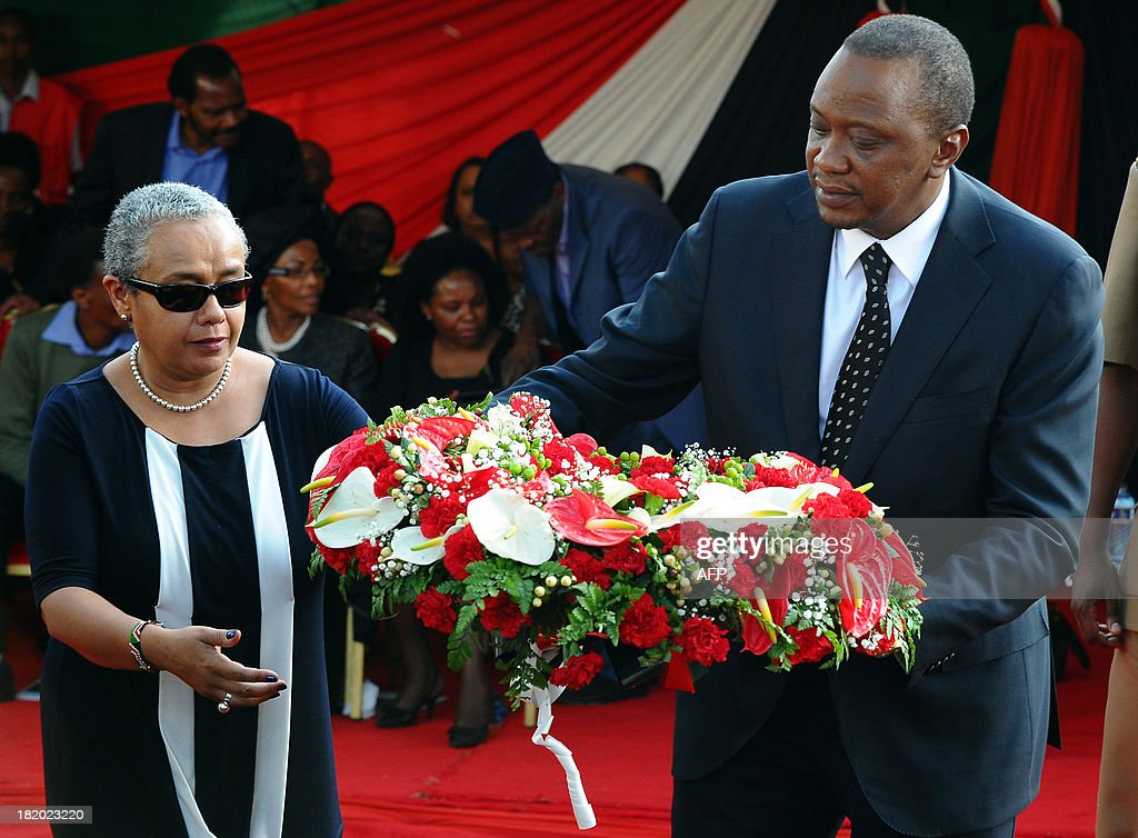 Kenyan President Uhuru Kenyatta and his wife Margaret lay a wreath of flowers during the funeral service of his nephew Mbugua Mwangi and his fiancee Rosemary Wahito in Nairobi on September 27, 2013 after they were both killed in the Westagte Mall attacks. Kenyan and foreign forensics teams scoured the wreckage of a Nairobi shopping mall for bodies and clues after a four-day siege by Islamist gunmen left 67 dead and dozens more missing. AFP PHOTO/JOHN MUCHACHA