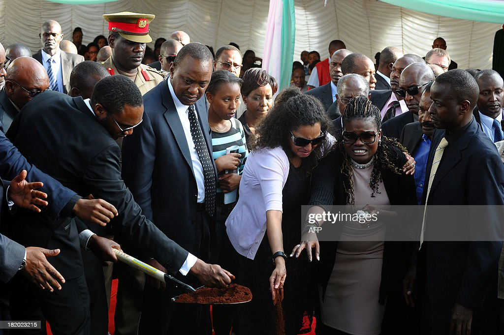 Kenyan President Uhuru Kenyatta (C) and other mourners attend the funeral service of his nephew Mbugua Mwangi and his fiancee Rosemary Wahito in Nairobi on September 27, 2013 after they were both killed in the Westagte Mall attacks. Kenyan and foreign forensics teams scoured the wreckage of a Nairobi shopping mall for bodies and clues after a four-day siege by Islamist gunmen left 67 dead and dozens more missing. AFP PHOTO/JOHN MUCHACHA