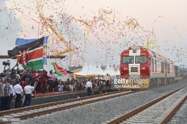 TOPSHOT Kenyan President Uhuru Kenyatta flags off a cargo train as it leaves the container terminal for its inaugural journey to Nairobi at the port...