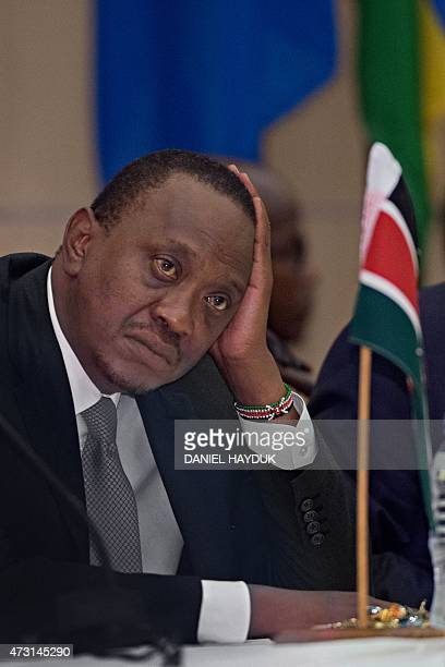 Kenyan president Uhuru Kenyatta listens at the State House in Dar es Salaam on May 13 2015 as Tanzanian President and East African Community chair...