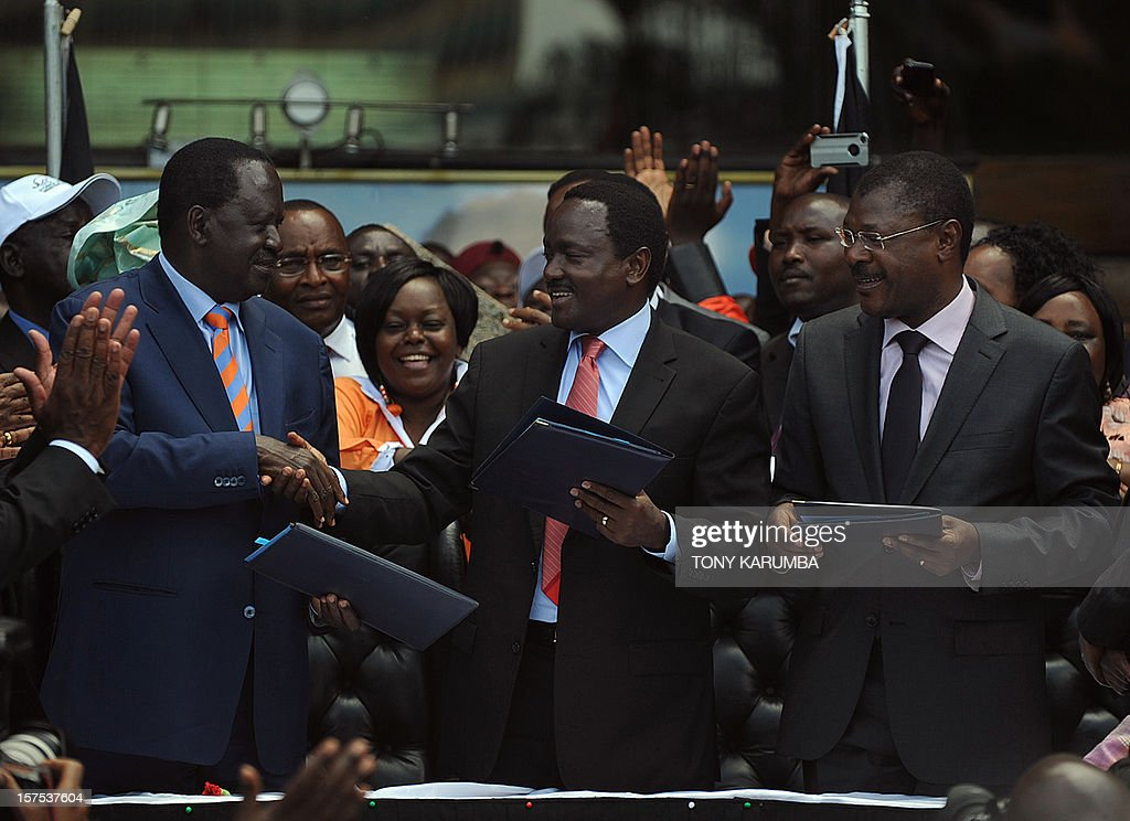 Kenyan Prime Minister Raila Odinga (L) exchanges signed agreements with Vice President Kalonzo Musyoka (C) and Trade Minister Moses Wetangula after announcing a powerful alliance on December 04, 2012 as running mates in presidential elections due in March 2013. The former rivals along leaders of 10 other smaller parties, signed an agreement in front of thousands of supporters to form the Coalition for Reform and Democracy (CORD) party. Odinga is widely tipped to be the presidential candidate with Musyoka as his deputy, although no formal announcement was made.