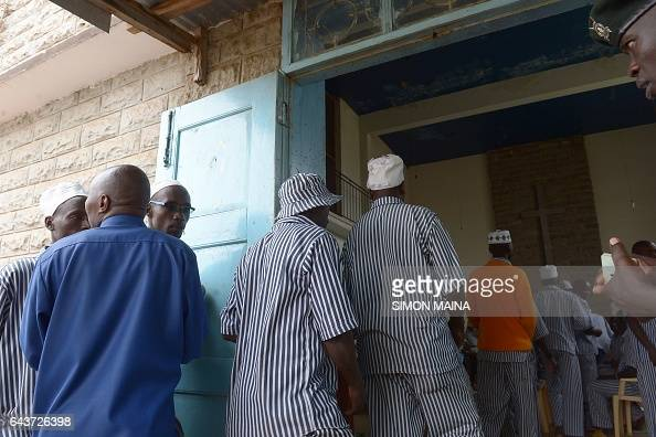 A Kenyan prison guard watch over prisoners as they queue to register with members of the Independent Electoral and Boundaries Commission to vote for...