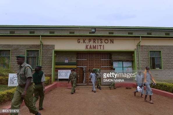 Kenyan prison warders and prisoners walk past the entrance of the Kamiti Prison in Nairobi on February 22 2017 At least 22 million voters are...