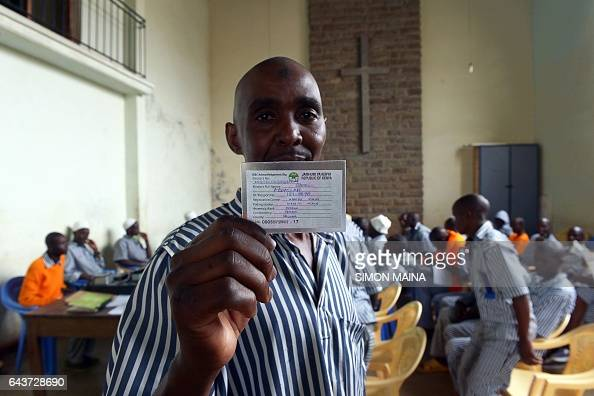 A Kenyan prisoner shows a voter card after registering with Independent Electoral and Boundaries Commission to vote for this year Kenyan general...