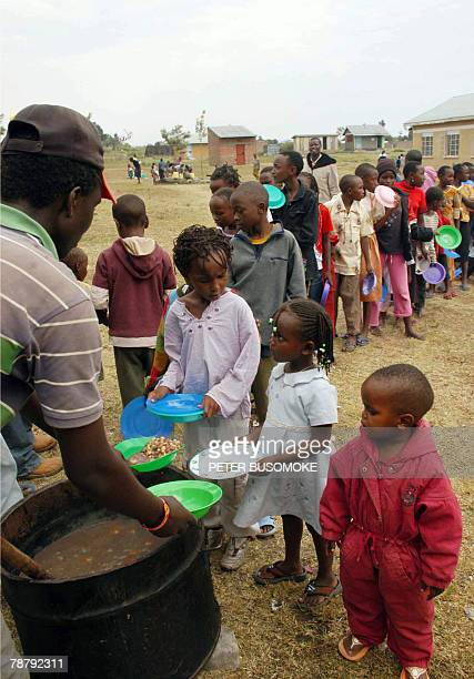 Kenyan refugee children from the Kikuyu tribe stand in line to receive food at Malaba's St Jude Primary School on the UgandaKenya border 05 January...