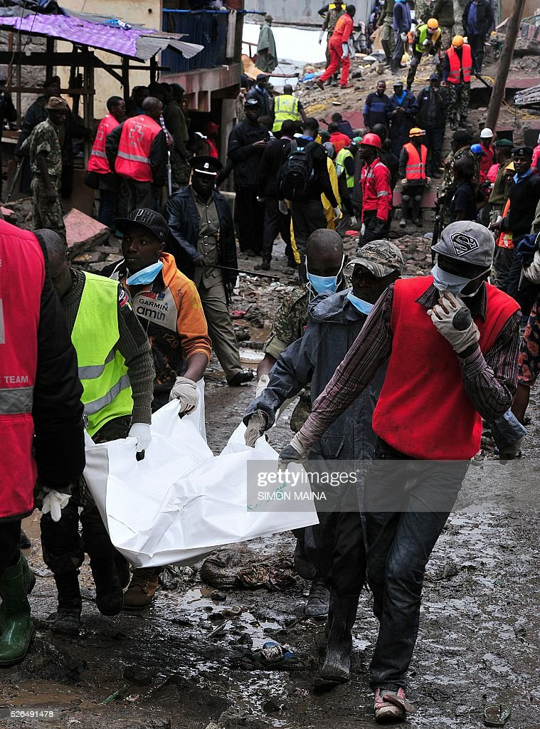 Kenyan rescue workers carry a body after a building collapsed in Nairobi on April 30, 2016. Torrential rainstorms in the Kenyan capital have left at least 14 people dead, police said, including at least seven crushed when a six-storey building collapsed, as rescue teams shifted rubble in a desperate search for survivors. / AFP / SIMON