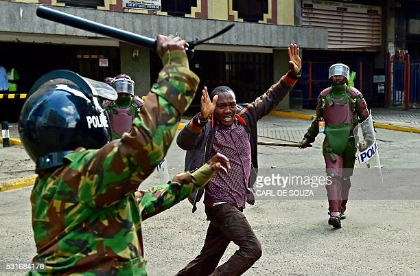 TOPSHOT Kenyan riot police officers raise batons over a man during a demonstration of Kenya's opposition supporters in Nairobi on May 16 2016...