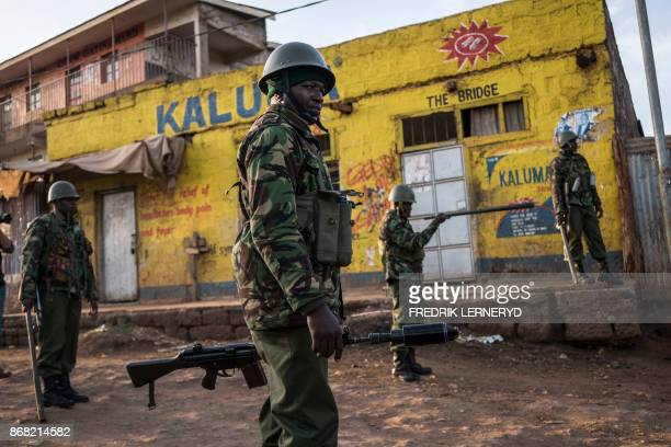 TOPSHOT Kenyan riot police patrol to clear an area previously blocked by Kenyan Opposition supporters at Kawangware in Nairobi on October 30 after...