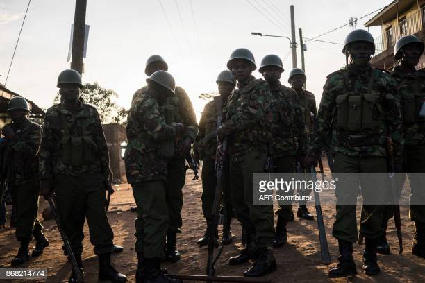 Kenyan riot police patrol to clear an area previously blocked by Kenyan Opposition supporters at Kawangware in Nairobi on October 30 after elections...