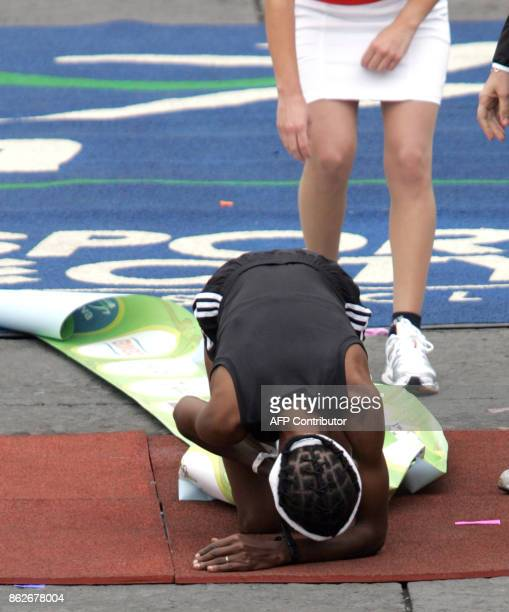Kenyan runner Anna Kibor rests for a few moments after crossing the finish line to win Mexico City's 25th International Marathon women clocking...