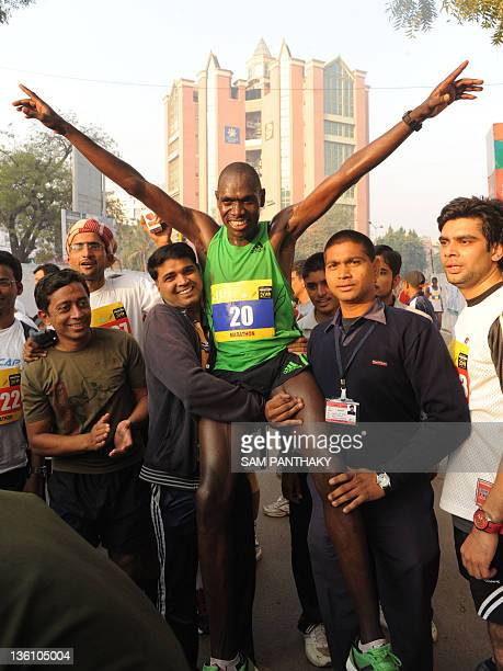 Kenyan runner Philemon Rotich celebrates after winning the Sabarmati Marathon 2011 in Ahmedabad on December 25 2011 Rotich finished first in the male...