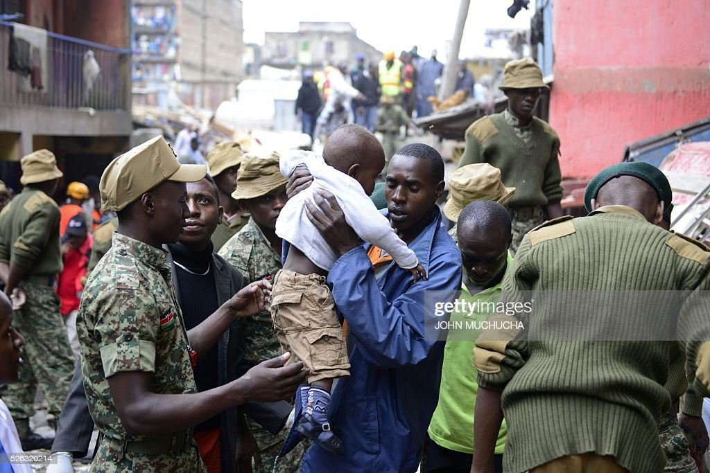 Kenyan security forces carry a boy as people are evacuated from the vicinity of a collapsed building in Nairobi on April 30, 2016. Torrential rainstorms in the Kenyan capital have left at least 14 people dead, police said, including at least seven crushed when a six-storey building collapsed, as rescue teams shifted rubble in a desperate search for survivors. / AFP / JOHN