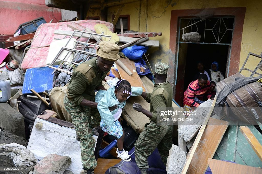 Kenyan security forces carry a girl as people are evacuated from the vicinity of a collapsed building in Nairobi on April 30, 2016. Torrential rainstorms in the Kenyan capital have left at least 14 people dead, police said, including at least seven crushed when a six-storey building collapsed, as rescue teams shifted rubble in a desperate search for survivors. / AFP / JOHN