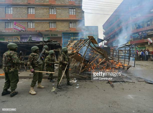 Kenyan security forces clear burning barricades at the Nairobi slum of Mathare in August 12 2017 following overnight protests by supporters of...