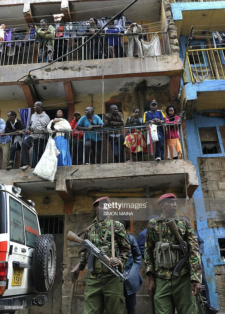 Kenyan security forces stand guard as residents observe the rescue efforts of a building collapse in Nairobi on April 30, 2016. Rescuers in the Kenyan capital made desperate efforts to free survivors including a woman and child trapped in a building that collapsed in storms that have left a total of 17 people dead. / AFP / SIMON