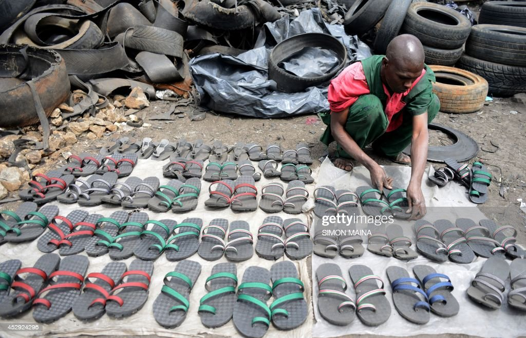 Kenyan shoemaker Munyao displays pairs of sandals locally known as 'Akalas' made from recycled tyres in the outskirts of Nairobi on July 30, 2014. Akala sandals have soles that are crafted from car tyres and are cushioned by rubber padding. They cost ten times less (between 2 and 5 US dollars) and last ten times longer than the average footwear in local shops.