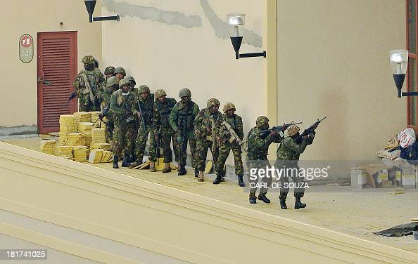 Kenyan soldiers move in formation as smoke rises in the background clearing the top floor balcony and interior of Westgate Mall on September 24 2013...