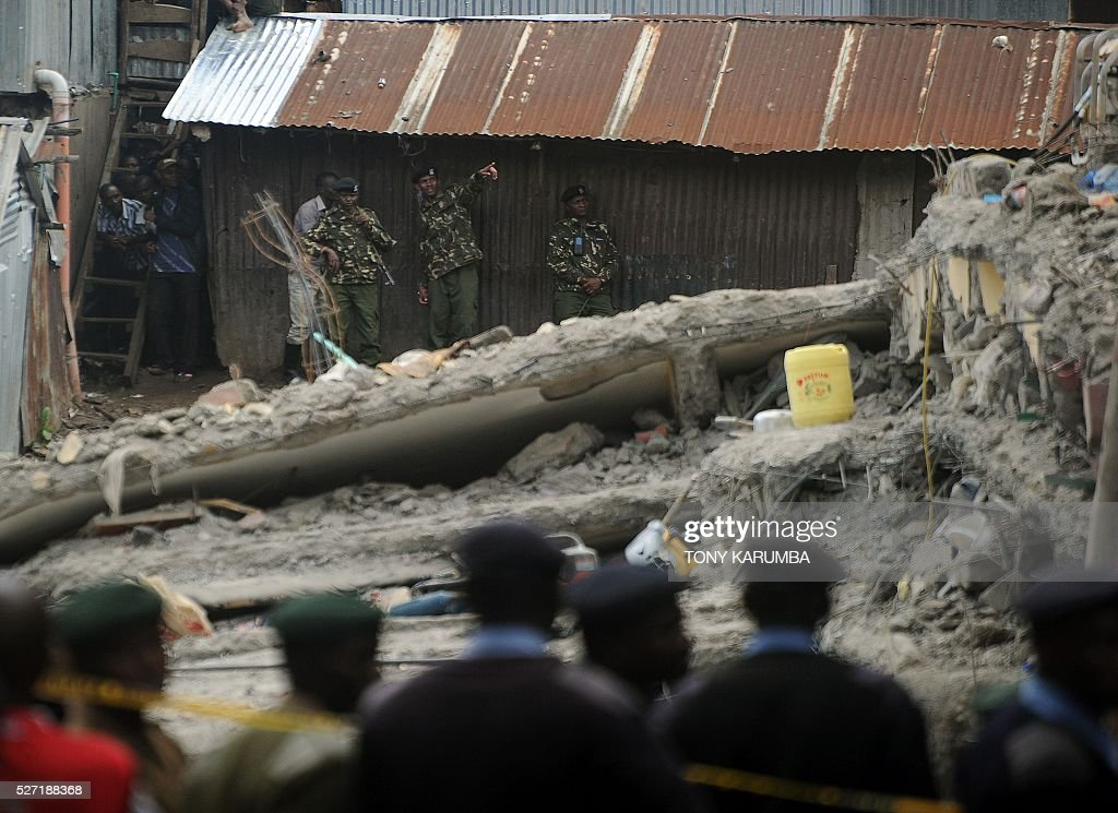 Kenyan soldiers stand on May 2, 2016 near the scene of a collapsed residential building in the low-income suburb of Huruma in Nairobi. The death toll in the collapse of a six-storey building in Nairobi on April 29 rose to 21 on May 2 after four more bodies were pulled from the rubble of the residential structure that gave way during weekend storms. / AFP / TONY