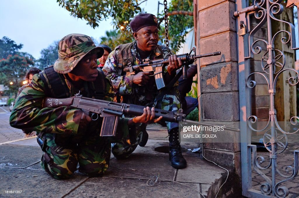 Kenyan soldiers take cover after heavy gunfire near Westgate mall in Nairobi on September 23, 2013. Kenyan Defence troops remain inside the mall, in a standoff with Somali militants after they laid siege to the shopping centre shooting and throwing grenades as they entered. Somali Shebab militants on September 23 threatened to kill hostages they are holding in the Nairobi shopping mall as Kenyan troops move to end their siege. AFP PHOTO / CARL DE SOUZA