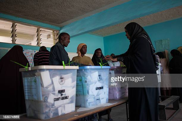 Kenyan Somali ladies cast their ballot papers in the Eastleigh district of the Kenyan capital Nairobi on March 4 2013 during the nationwide elections...