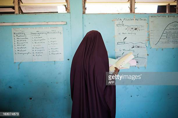 Kenyan Somali lady walks with her ballot cards in the Eastleigh district of the Kenyan capital Nairobi on March 4 2013 during the nationwide...