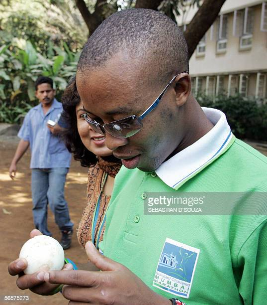 Kenyan visually impaired athlete Henry Wanyoike feels a cricket ball before playing cricket with visually impaired students of the Victoria Memorial...