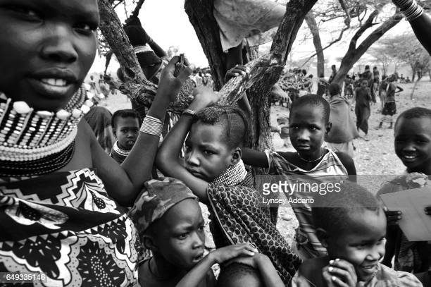 A Kenyan woman and several children await food handouts and nutrition checks by Doctors Without Borders during an ambulatory therapeutic feeding...