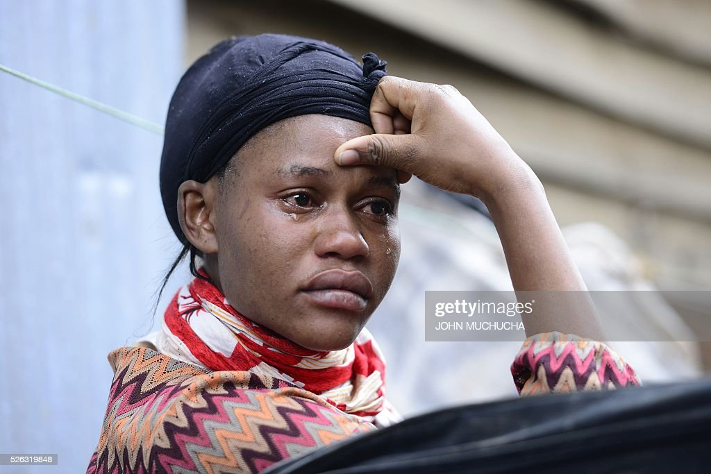 A Kenyan woman cries as she looks at what used to be her home after a building collapsed in Nairobi on April 30, 2016. Torrential rainstorms in the Kenyan capital have left at least 14 people dead, police said, including at least seven crushed when a six-storey building collapsed, as rescue teams shifted rubble in a desperate search for survivors. / AFP / JOHN